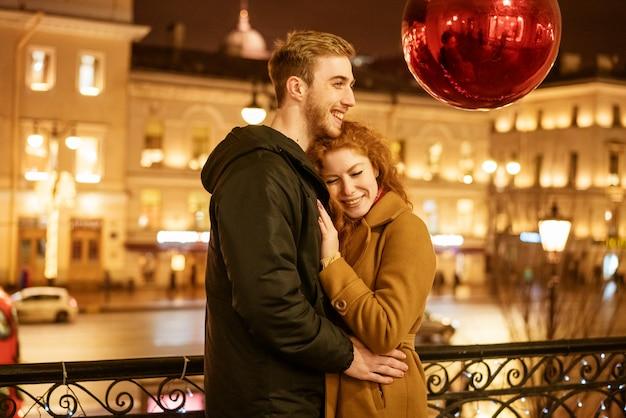 Una feliz pareja se encuentra abrazada en la calle por la noche bajo las luces festivas