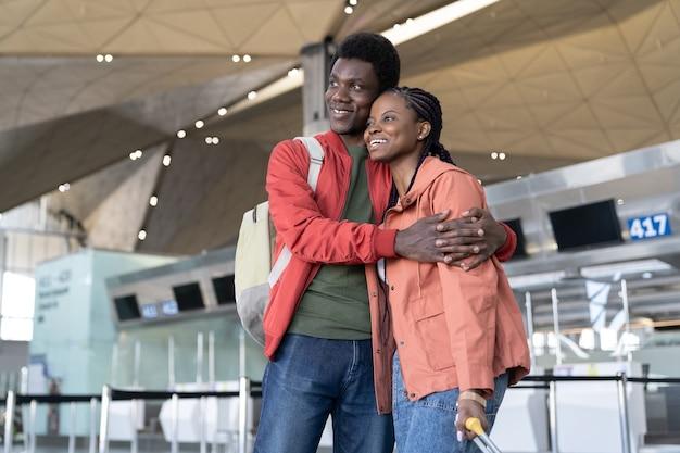 Feliz pareja espera avión en el aeropuerto