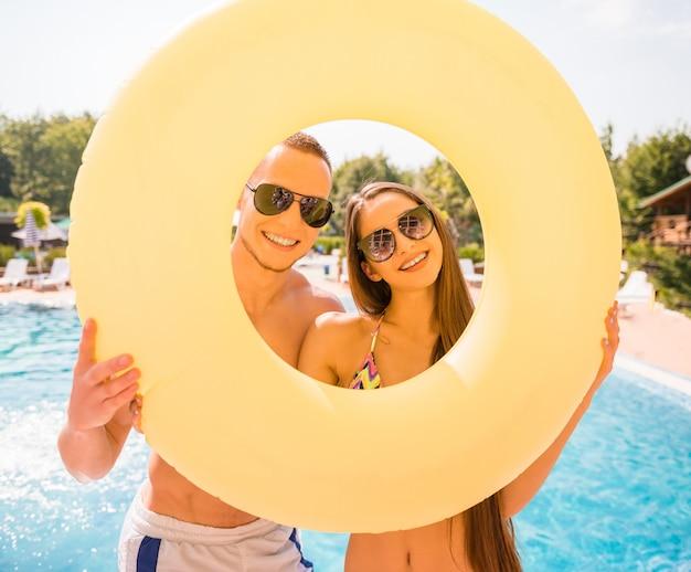 Feliz pareja están posando con anillo de goma en la piscina.
