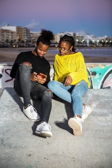 Feliz pareja étnica navegando por teléfono en la calle