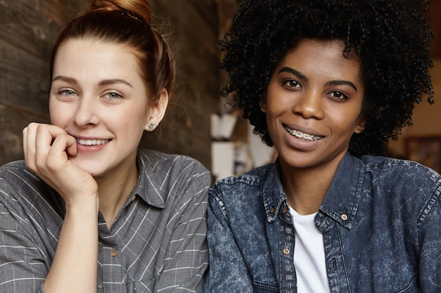 Feliz pareja femenina interracial homosexual pasar tiempo agradable juntos en el interior