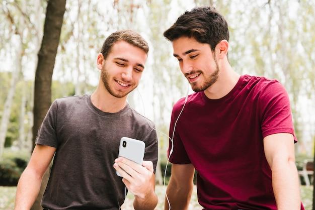 Feliz pareja gay en auriculares escuchando música en el móvil en el parque