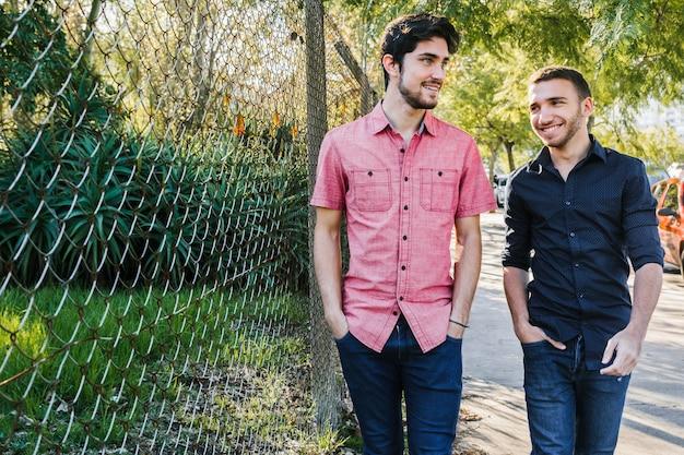 Feliz pareja gay caminando a lo largo de la cerca a la luz del día