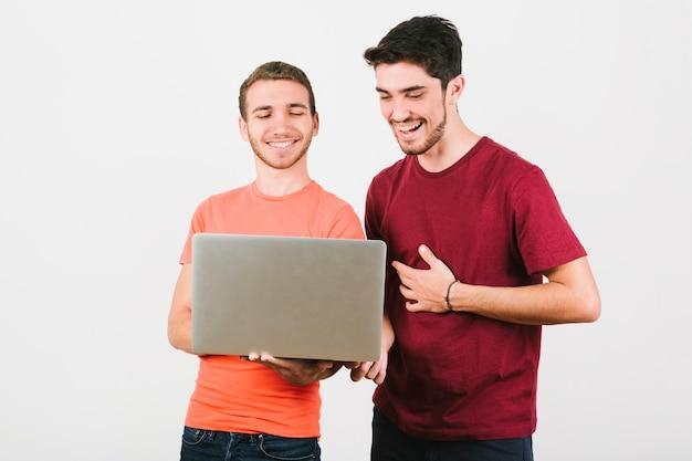 Feliz pareja gay mirando cuaderno