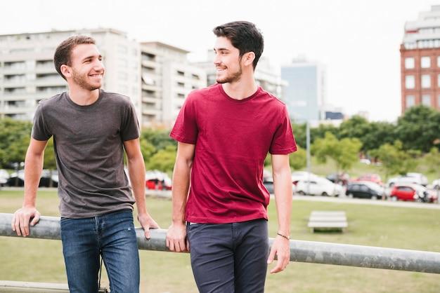 Feliz pareja gay de pie junto a la barandilla