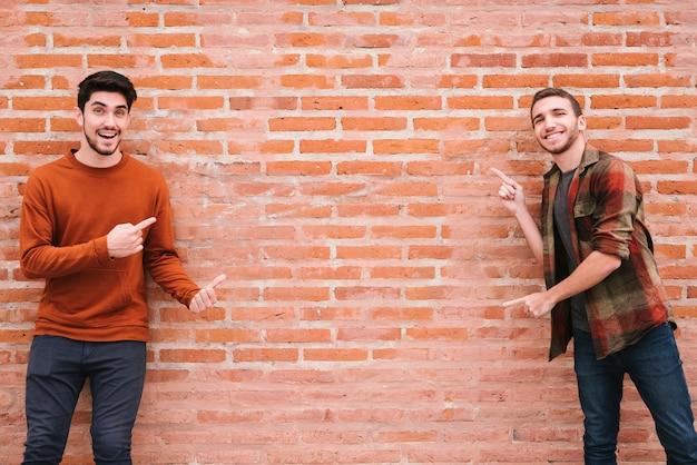 Feliz pareja gay de pie junto a la pared de ladrillo y apuntando con los dedos