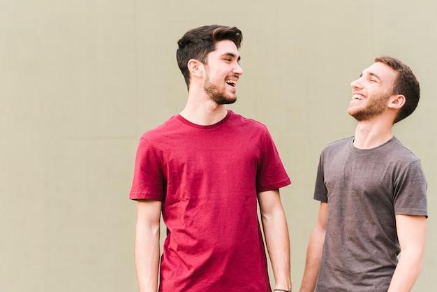 Feliz pareja gay de pie y riendo