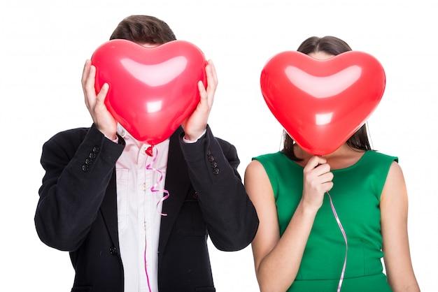 Feliz pareja con globos en lugar de una cabeza.