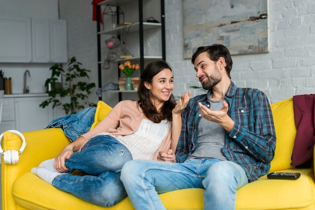 Feliz pareja hablando en el sofá