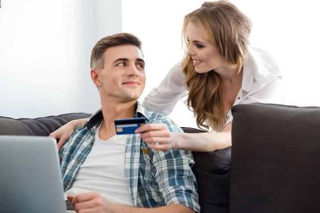 Feliz pareja haciendo compras en internet usando una computadora portátil y una tarjeta de crédito sentado en el sofá en la sala de estar