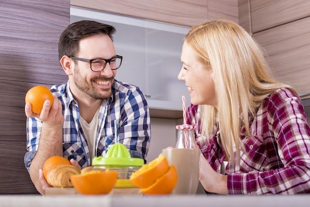 Feliz pareja haciendo jugo de naranja natural en la cocina y disfrutando de su tiempo