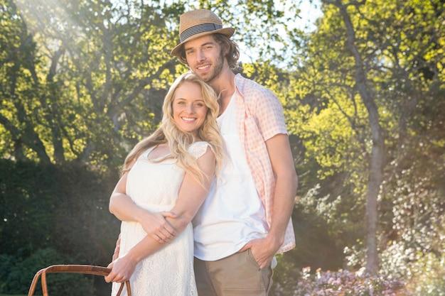 Feliz pareja haciendo un picnic y abrazándose en el jardín