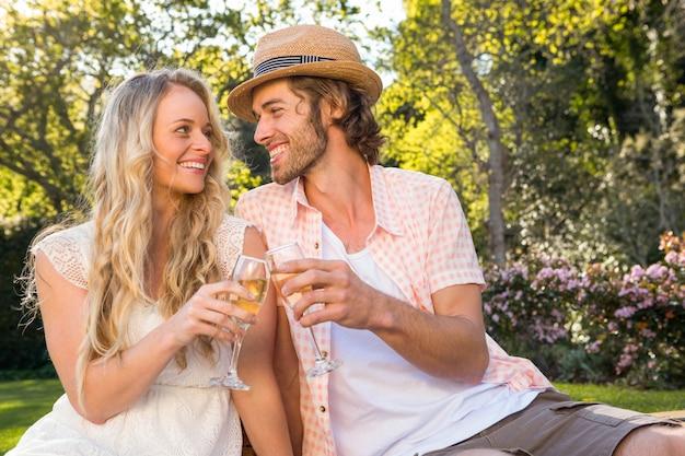 Feliz pareja haciendo un picnic y beber champán en el jardín