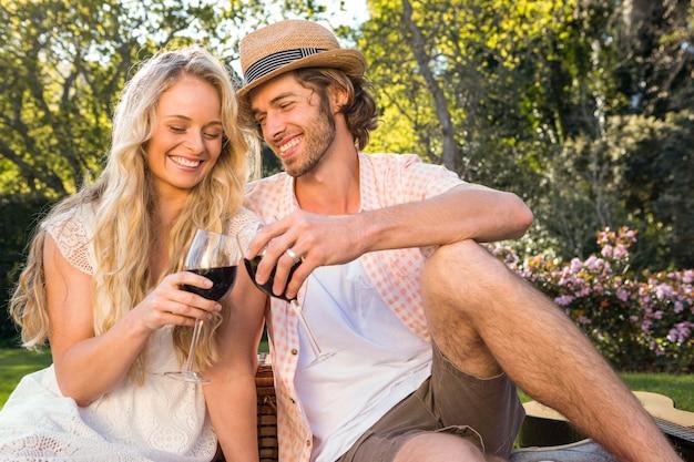 Feliz pareja haciendo un picnic y beber vino tinto en el jardín