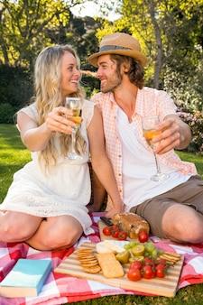 Feliz pareja haciendo un picnic en el jardín