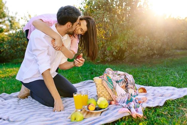 Feliz pareja haciendo un picnic en el parque en un día soleado, besándose y abrazándose
