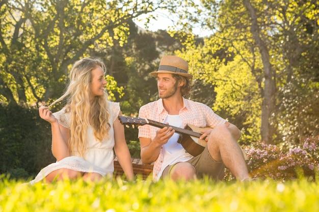 Feliz pareja haciendo un picnic y tocando la guitarra en el jardín