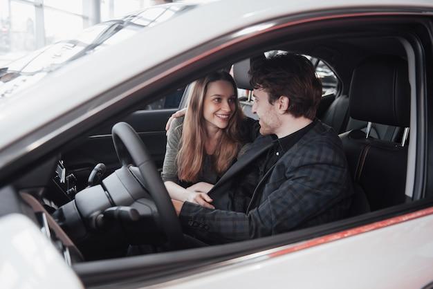 Feliz pareja hermosa está eligiendo un auto nuevo en el concesionario