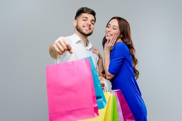Feliz pareja hombre y mujer con bolsas de compras aisladas