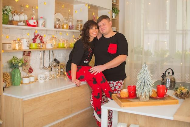 Feliz pareja hombre y mujer en la cocina en navidad