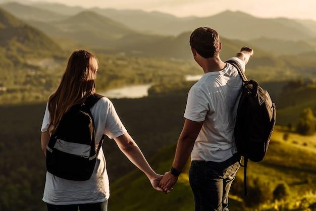 Feliz pareja hombre y mujer disfrutan del valle de la montaña y el río