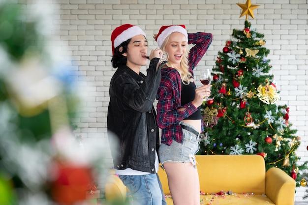 Feliz pareja de hombre y mujer joven con copas de champán en la mano bailando en navidad