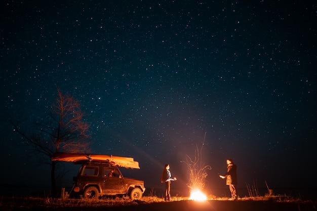 Feliz pareja hombre y mujer de pie delante de la hoguera ardiente