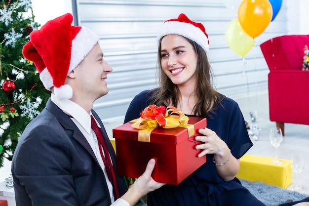 Feliz pareja intercambiando regalos de navidad