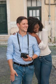 Feliz pareja interracial caminando en la ciudad