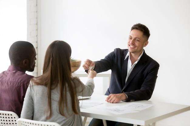 Feliz pareja interracial recibiendo las llaves de la nueva casa de la inmobiliaria