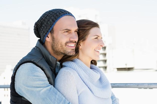 Feliz pareja joven abrazando y sonriendo al aire libre