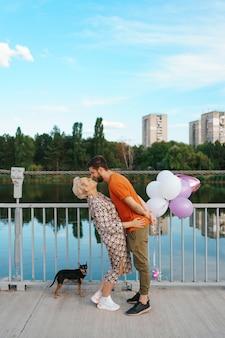 Feliz pareja joven abrazándose y besándose en el puente sosteniendo globos rosas y perro con ciudad en el horizonte