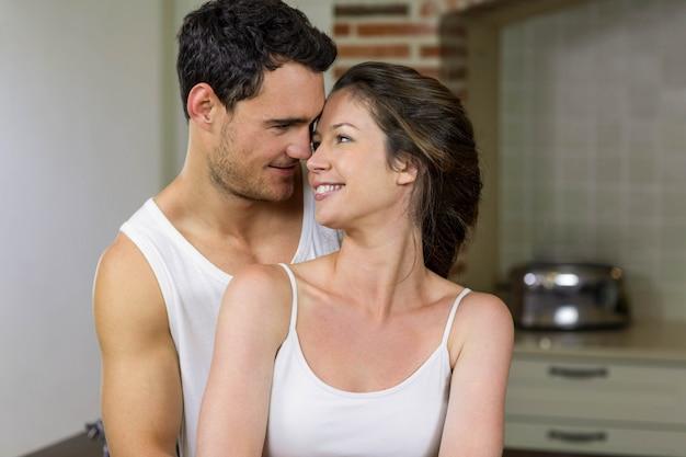 Feliz pareja joven abrazándose en la cocina