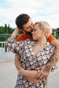 Feliz pareja joven abrazándose y riendo al aire libre.