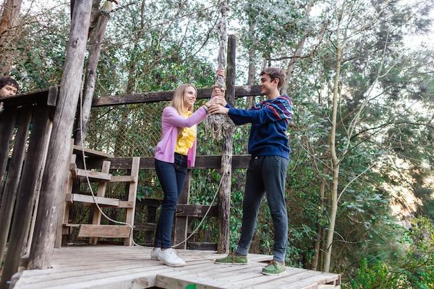 Feliz pareja joven agarrando una cuerda