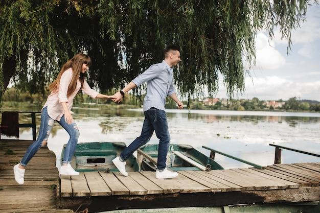 Feliz pareja joven al aire libre. pareja joven amor corriendo un puente de madera tomados de la mano.