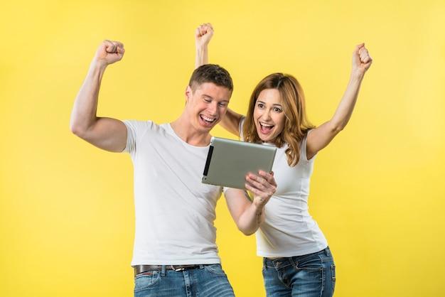 Feliz pareja joven apretando su puño mirando tableta digital riendo