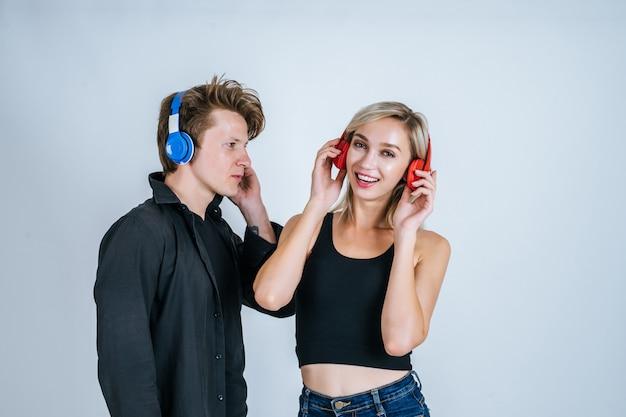 Feliz pareja joven en auriculares escuchando música
