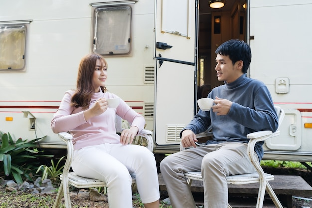 Feliz pareja joven bebiendo café delante de una autocaravana autocaravana rv