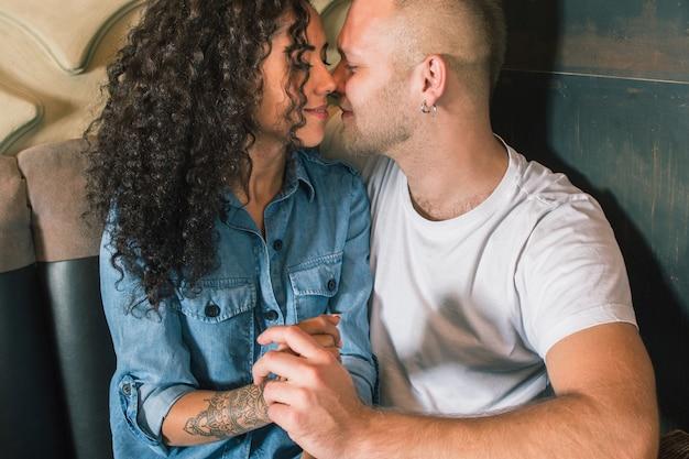 Feliz pareja joven está bebiendo café y sonriendo mientras está sentado en el café