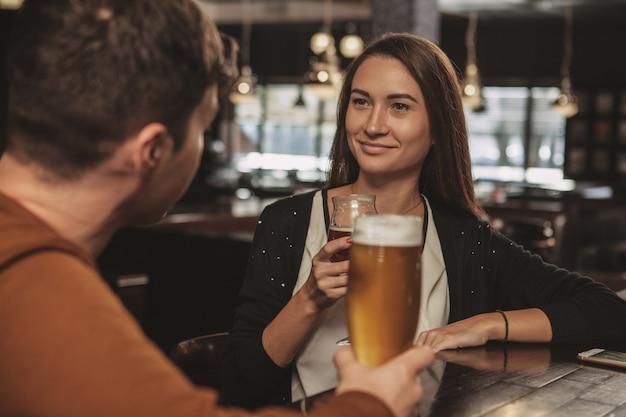 Feliz pareja joven bebiendo cerveza en una cita en el bar