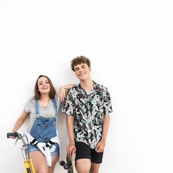 Feliz pareja joven con bicicleta y patín sobre fondo blanco