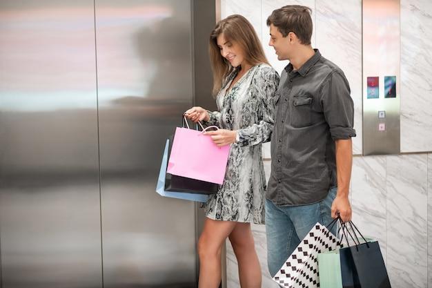 Feliz pareja joven con bolsas de compras pasa por el ascensor, el chico mira con entusiasmo a la niña sonriente que abre la bolsa de compras. compras. deleite. rebaja.
