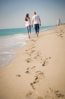 Feliz pareja joven caminando por una playa tropical durante su luna de miel