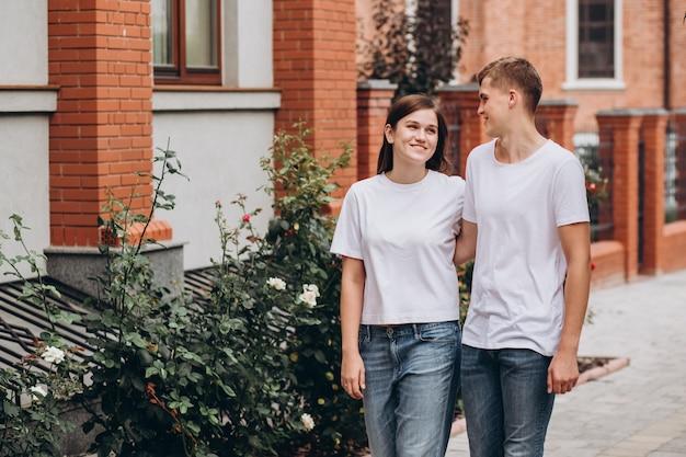 Feliz pareja joven en camisetas blancas y jeans camina por las calles de la ciudad y se dan la mano.