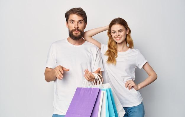 Feliz pareja joven en camisetas blancas con paquetes en las manos