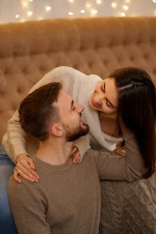 Feliz pareja joven casada abrazándose, sentados juntos en el acogedor sofá