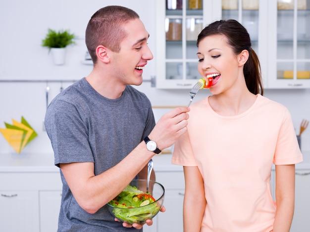 Feliz pareja joven comiendo ensalada en la cocina