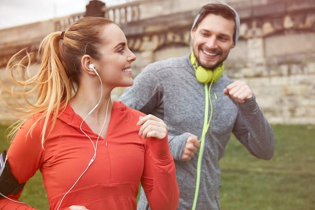 Feliz pareja joven corriendo al aire libre