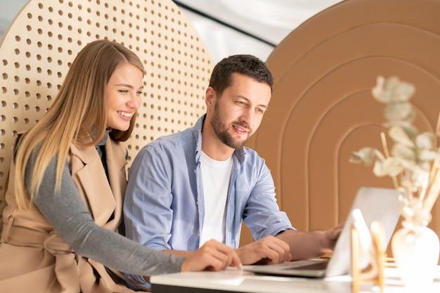 Feliz pareja joven descansando mirando la pantalla del portátil mientras ve cosas curiosas por mesa en la acogedora cafetería